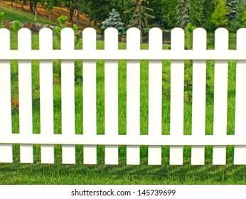 White fence in garden against green grass.