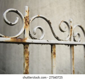 A white fence which has become rusted through years of neglect