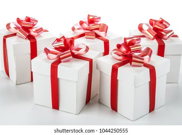 white festive gift boxes with red bows on a white