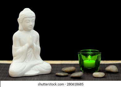 White figure in meditation pose with pebbles and candle in a green glass from point of view