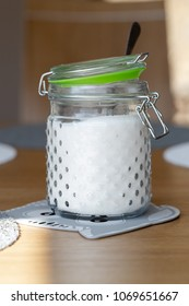 White fine sugar in retro large glass jar on table in dining room. Vertical close up crop