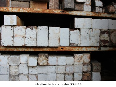 White fire bricks from a kiln stacked on rusty metal shelves.