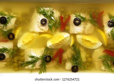 White fish aspic with egg, paprika, olive, dill, lemon, peas
