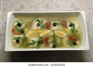 White fish aspic with egg, paprika, olive, dill, lemon, peas in white pot on linene background
