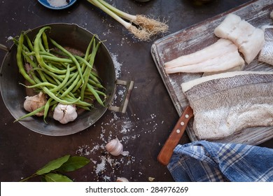 A white fish fillet with fresh vegetables over a dark rustic table with retro kitchen tools. Healthy and mediterranean food and diet. Rustic style.