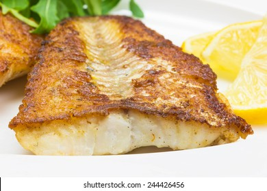 White fish with lemon and arugula on white plate, selective focus