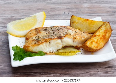 White fish with potato wedges, lemon and celery on white plat, wooden background