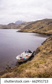 White fishing boat near the shore of a wild loch in a remote area of the Scottish highlands. Nobody on the scene.