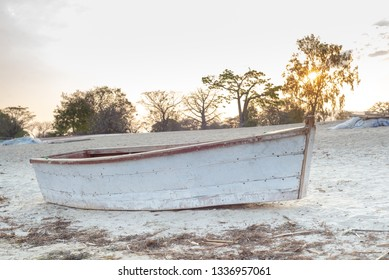 A white fishing boat rests on the beach next to lake Malawi at the end of the day