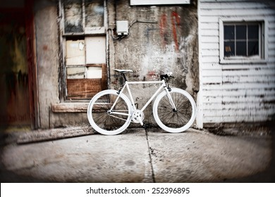 White fixie bicycle against a grunge wall in an alley.