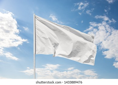 White flag against a blue sky with clouds fluttering in the wind