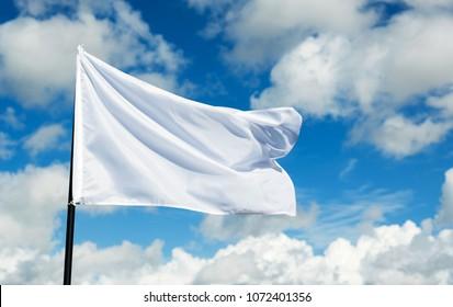 White flag flying against blue sky.