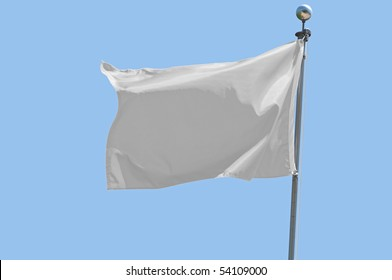 White flag flying in a stiff breeze against a clear blue sky.