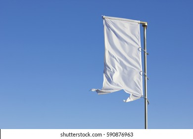 White flag raised over a cloudless blue sky.