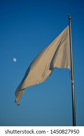 White flag waiving against blue sky. Moon visible in the background. Surrender Flag flowing in the wind. Beautiful sky, vivid moon, flag flap and wave. Scenic peaceful ideal image. Sun cast.
