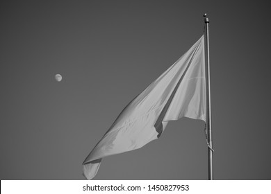 White flag waiving against blue sky in black and white. Moon visible in the background. Surrender Flag flowing in the wind. Beautiful sky, vivid moon, flag flap and wave. Scenic peaceful ideal image.
