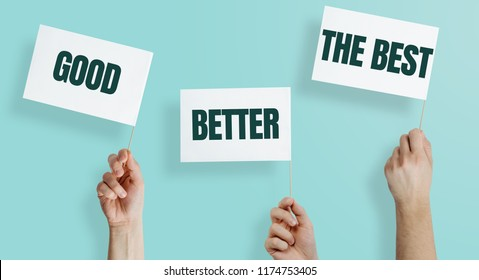 White flags with the words GOOD, BETTER, THE BEST kept in hands on a blue, pastel background. The concept of being better, developing skills, doing a better job.