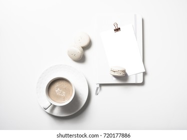 White flat lay with beige macaroons, coffee cup, notepad and pos