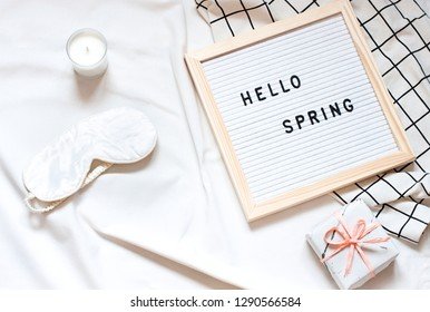 """White flat lay on the bed blanket with text """"Hello Spring"""". Concept seasonal top view  card"""
