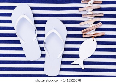 White flip flop shoes and fish decoration on blue white striped beach mat background, top view. White Toe sandals, flat lay. Summer background with flipflop shoes, flatlay