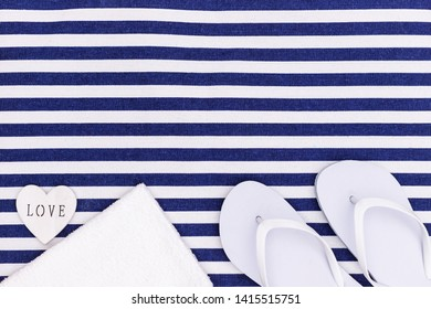 White flip flop shoes and towel on blue white striped beach mat background, top view, with copy space. White Toe sandals, flat lay, text place. Summer background with flipflop shoes, flatlay