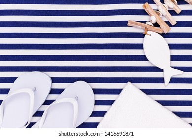 White flip flop shoes and towel on blue white striped beach mat background, top view, copy space. White Toe sandals, flat lay, text place. Summer background with flipflop shoes, flatlay