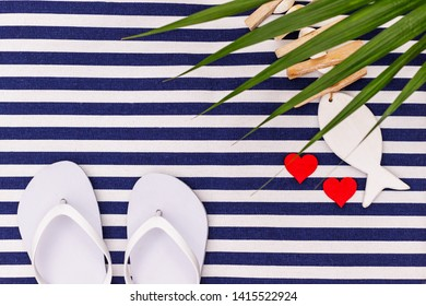 White flip flops shoes and fish on blue white striped beach mat background, top view, with copy space. White Toe sandals , flat lay, text place. Summer background with flipflop shoes, flatlay