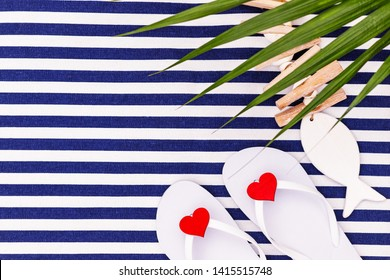 White flip flops shoes with red heats on blue white striped beach mat background, top view, with copy space. White Toe sandals , flat lay, text place. Summer background with flipflop shoes, flatlay