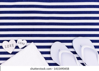 White flip flops shoes and towel on blue white striped beach mat background, top view, with copy space. White Toe sandals , flat lay, text place. Summer background with flipflop shoes, flatlay