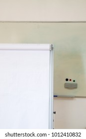 White flipchart with blank page in the foreground and whiteboard.