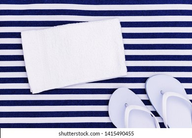 White flipflops shoes and towel on blue white striped beach mat background, top view, with copy space. White Toe sandals, flat lay, text place. Summer background with flip flop shoes, flatlay