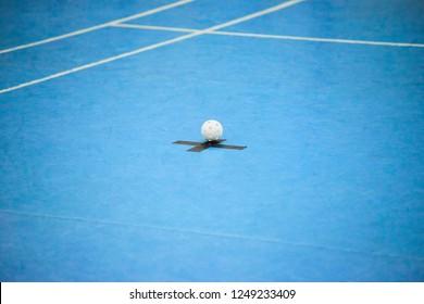 White floorball ball on blue surface