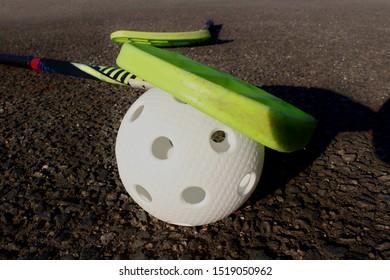 White floorball with green floorball stick lying on tar ground