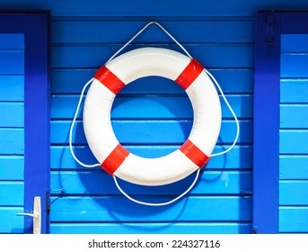 White flotation ring on the blue wall near boat rental