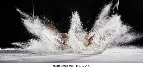 White flour flying into air as pastry chef in black suit slams ball dough on white powder covered table