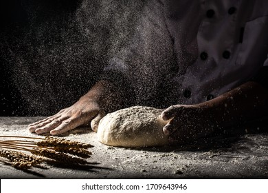 White flour flying into air as pastry chef in white suit slams ball dough on white powder covered table. concept of nature, Italy, food, diet and bio.