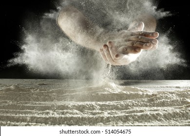 white flour on black background and hands