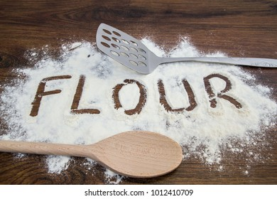 White flour on cooking table with utensils. Word flour written on the table.
