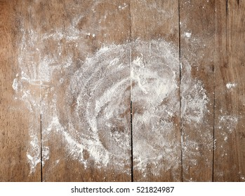 white flour on rustic wooden table, top view