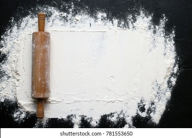 white flour with a rolling pin on a black background