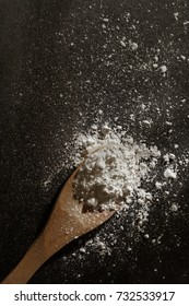 white flour in a wooden spoon lie on  black background. row food background