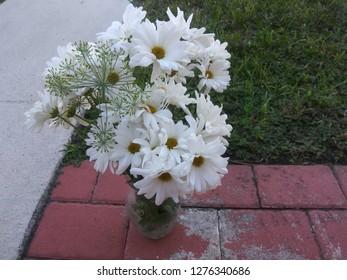 White flower arrangent against brick tile and pavement background