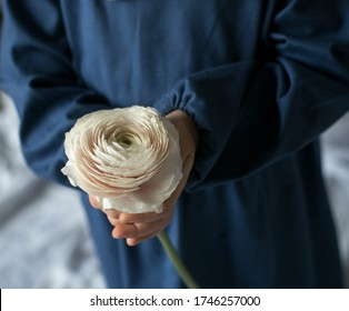 White flower in the baby's hands. Care for the world and their loved ones. Cildren's hands. Charity in our world. Roses and spring flower in waffle icecream horn. Baby in blue dress. Volunteer world.