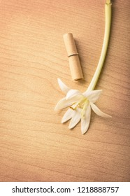 A white flower with small roll of paper on wood backgroind, flat to view with copy space and vitage color style, Secret Love Letters Ideas concept