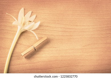 A white flower with small roll of paper on wood backgroind, flat to view with copy space and vitage color style, Love Letters Ideas concept