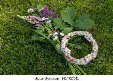 White flower wreath, solstice bouquet on a green grass background. Summer Solstice Day - Midsummer Day. Ligo night.