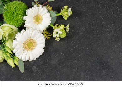 White flowers background / Top view of white fresh flowers on granite tombstone background. Funeral and condolences theme.