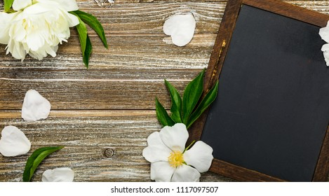 White Flowers with Black Chalkboard Background Card Concept, Top View. Selective focus.