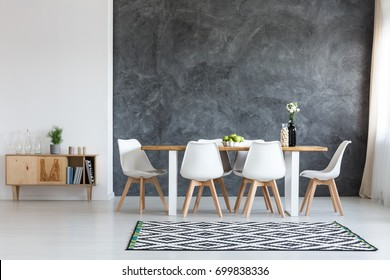 White flowers in black vase next to glass container with wine corks on dining table