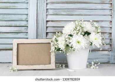 White flowers bouquet in bucket and empty photoframe on wood table against vintage wooden shutters. Shabby chic style.